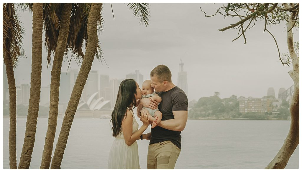 mother-and-father-kiss-the-child-sydney-photographer-photo