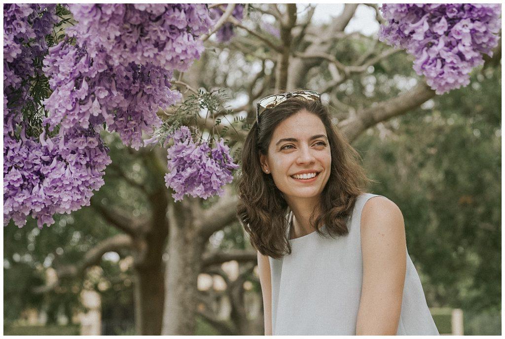 woman-smiles-under-jacaranda-tree-photo