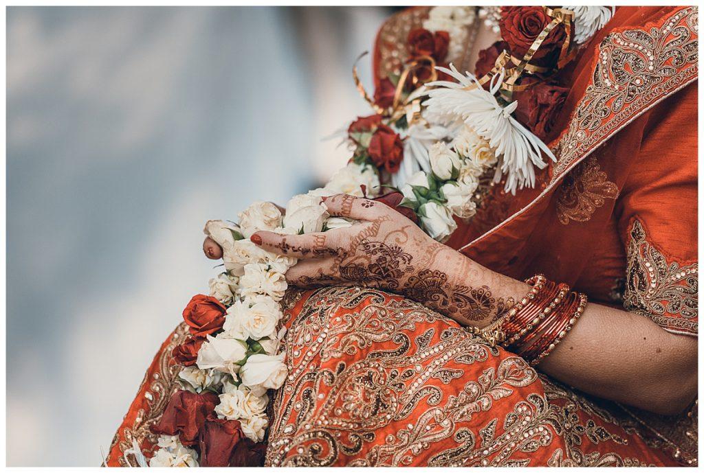 mehendi-on-brides-hands-holding-flower-garland-photo