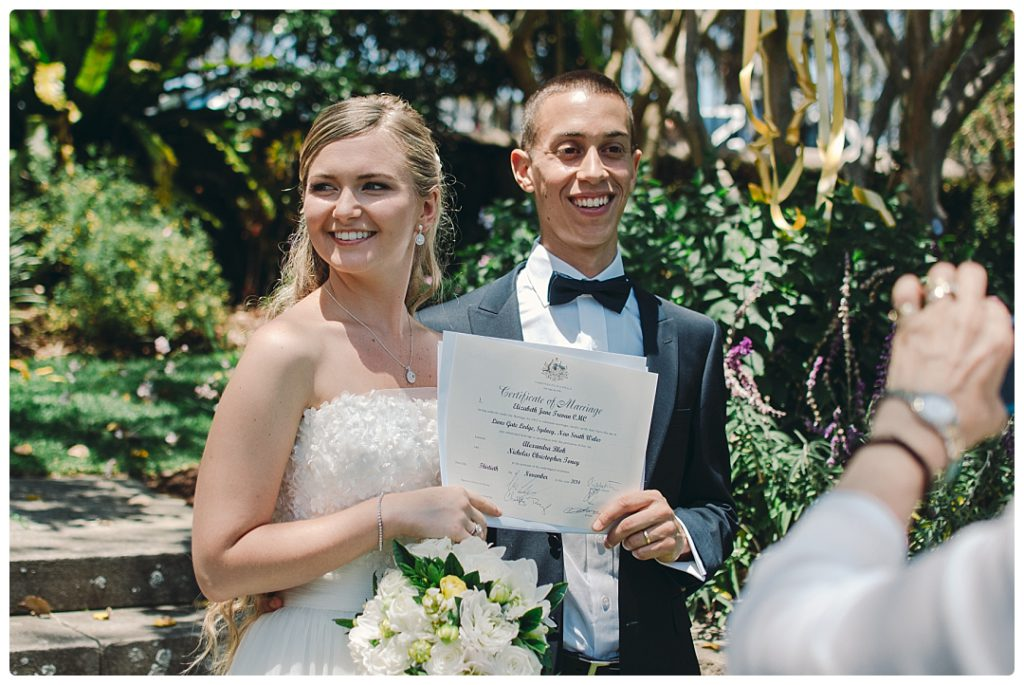 husband-and-white-holds-their-wedding-certificate-after-the-ceremony-photo